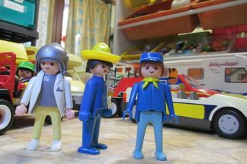 trois playmobil devant des vehicules